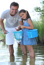 Father and daughter fishing by a lake Stock Images