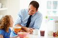 Father and daughter having breakfast in kitchen together looking at each other smiling Royalty Free Stock Images