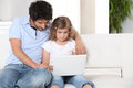 Father and daughter at home using a laptop Stock Image