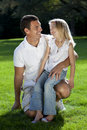 Father With Daughter On Knee Smiling In A Park Stock Images