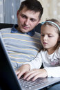 Father and daughter on laptop Stock Photos