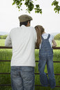 Father with daughter looking at lush landscape by fence rear view of a Royalty Free Stock Photography