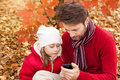 Father and daughter looking at the mobile phone in an autumn park while sitting outdoor enjoying modern technology Stock Images