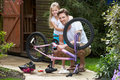 Father and daughter mending bike together smiling to camera Royalty Free Stock Photos