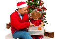 Father and daughter opening xmas gift together in front of tree Royalty Free Stock Photography