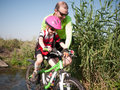 Father and daughter outdoors helping with her bicycle Stock Photography