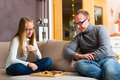 Father and daughter playing checkers parlor or board game on sofa Stock Photo