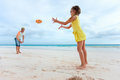 Father and daughter playing with flying disk at beach Royalty Free Stock Images