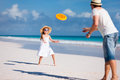 Father and daughter playing frisbee at beach Stock Image