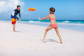 Father and daughter playing frisbee at beach Royalty Free Stock Images