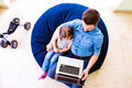 Father and daughter, playing on laptop, sitting on beanbag Royalty Free Stock Photo
