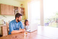 Father and daughter, playing on laptop, sitting in kitchen Royalty Free Stock Photo