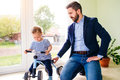Father and daughter playing together, riding a bike indoors Royalty Free Stock Photo