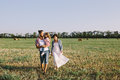 Father daughter and pregnant mother enjoying life outdoor in field a red plaid shirt white dress Stock Images