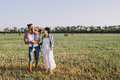 Father daughter and pregnant mother enjoying life outdoor in field a red plaid shirt white dress Royalty Free Stock Photography