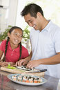 Father And Daughter Preparing Sushi Together Royalty Free Stock Photos