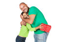 Father and daughter pretty cute caucasian girl wearing a green long sleeve top blue jeans her he is giving her a gift in red Royalty Free Stock Photo