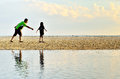 A father and daughter running along the beach in sunset Stock Photography