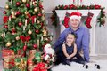Father and daughter sit near the Christmas tree. Father have a Santa Claus hat on his head. A fireplace behind them Royalty Free Stock Photo