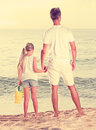 Father with daughter standing back