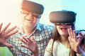 Father and daughter in virtual reality glasses having fun