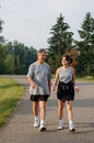 Father and daughter walking senior middle aged taking a walk down a road Royalty Free Stock Photo