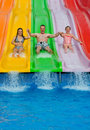 Father with daughters on tropical slide and swimming pool slides Royalty Free Stock Photography