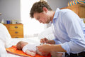 Father Dressed For Work Changing Baby's Diaper In Bedroom Royalty Free Stock Photo