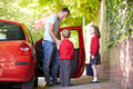 Father driving to school with children dropping them off saying goodbye Stock Photo