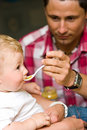 Father feeding baby Royalty Free Stock Images