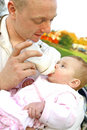 Father feeding his baby girl with a bottle of milk Stock Image