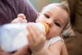 Father feeding milk to baby girl