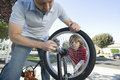 Father fixing son s bicycle tyre closeup of a cropped Stock Photography