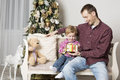 Father gives christmas gift to his son and with tree in the background Royalty Free Stock Photography