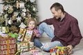 Father gives christmas gift to his son and with tree in the background Stock Images