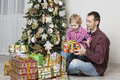 Father gives christmas gift to his son and with tree in the background Royalty Free Stock Photo