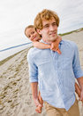 Father giving daughter piggy back ride at beach Stock Images