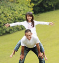 Father giving daughter piggyback ride Stock Photo