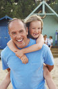 Father giving daughter piggyback ride portrait of on beach Royalty Free Stock Image
