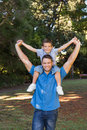 Father giving son piggy back and stretching out their arms smiling at camera in the park Stock Images