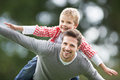 Father giving son piggyback in countryside smiling to camera Royalty Free Stock Image