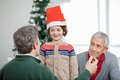 Father and grandfather looking at son during happy wearing santa hat christmas home Royalty Free Stock Photos
