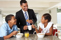 Father having breakfast with children before work smiling Stock Photos