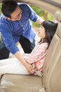 Father help daughter to fasten a seat belt in car Royalty Free Stock Photos