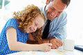 Father helping daughter with homework in kitchen looking at textbook smiling Stock Photos