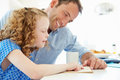Father helping daughter with homework in kitchen sitting at table looking at textbook Royalty Free Stock Photography