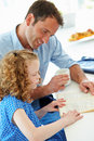Father helping daughter with homework in kitchen whilst holding hot drink looking at book Stock Photos