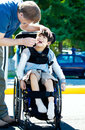 Father helping disabled child in wheelchair has cerebral palsy Royalty Free Stock Photos