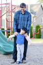 Father helping disabled son at playground Royalty Free Stock Image