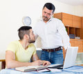 Father helping his son adult to do homework focus on the left man Royalty Free Stock Photography
